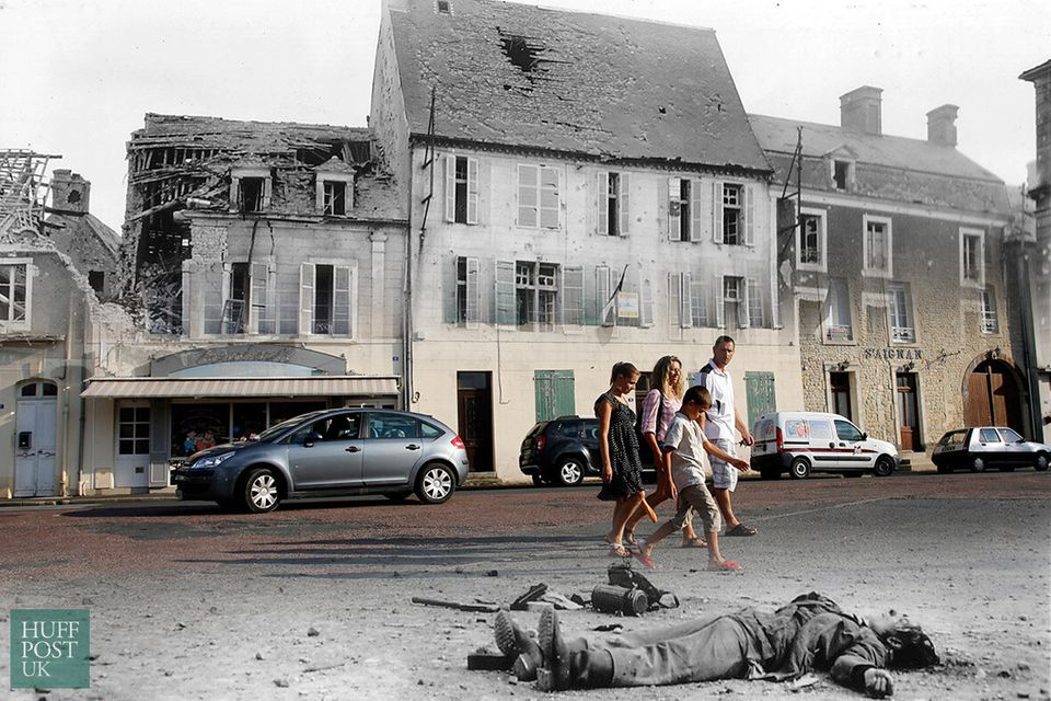 Tourists walk by where the body of a dead German soldier once lay in the main square of Place Du Marche...