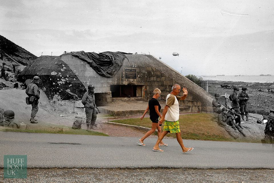 Beach goers walk past a captured German bunker overlooking Omaha Beach near Saint Laurent sur