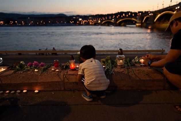 한 아이가 다뉴브강가에 마련된 사고 희생자 추모 공간에 초를 놓고