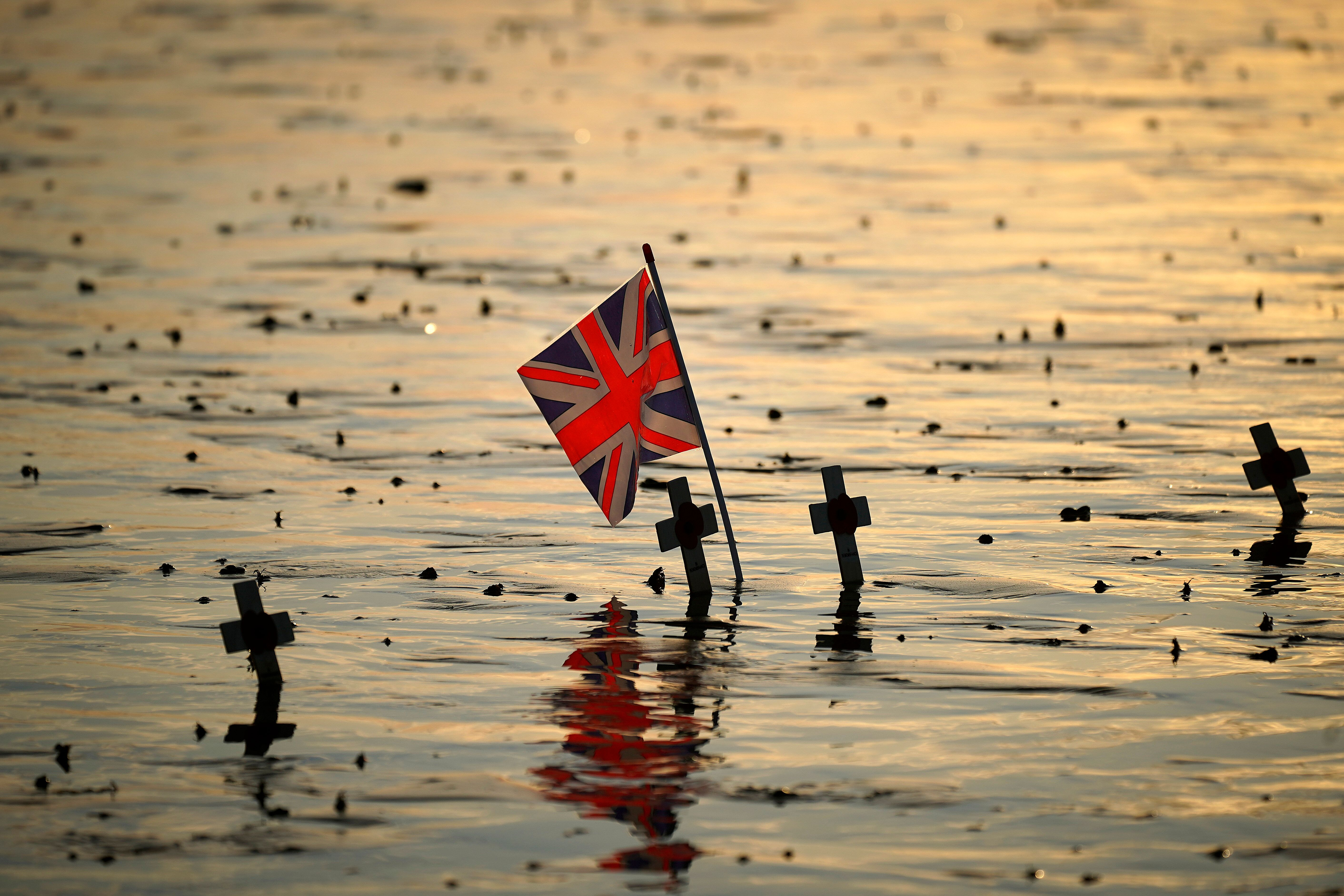 ARROMANCHES LES BAINS, FRANCE - JUNE 6: A Union Flag is planted alongside crosses on Gold Beach near the Mulberry harbour on the morning of the 75th anniversary of the D-Day landings on June 6, 2019 in Arromanches Les Bains, France. June 6th is the 75th anniversary of the D-Day landings which saw 156,000 troops from the allied countries including the United Kingdom and the United States join forces to launch an audacious attack on the beaches of Normandy, these assaults are credited with the eventual defeat of Nazi Germany. (Photo by Christopher Furlong/Getty Images)