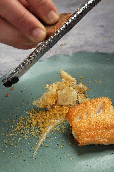 ▲主菜「加拿大黑鱈魚」野生的黑鱈魚肉質細緻柔順,多汁且香味濃郁,在鐵板上煎到表面金黃,一咬下鮮美魚汁汨汨流出,滋味迷人,一旁襯著炸過的菊芋脆片、菊芋泥,上桌後現場再大方刨上烏魚子,高級感與美味同時瞬間升級,鮮上加鮮。