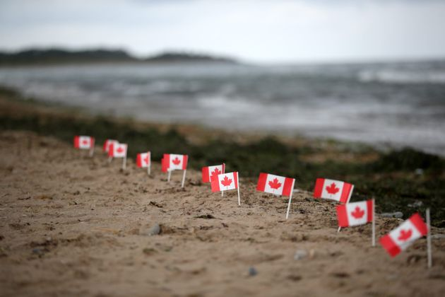 Canadian flags are seen here placed along the shoreline on Juno Beach in Courseulles-sur-Mer, France,...