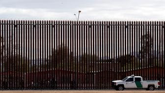 In this April 5, 2019, photo, a U.S. Customs and Border Protection vehicle sits near the a section of the U.S. border wall with Mexico in Calexico, Calif. Democrats controlling the House are trying to use a popular veterans measure to block President Donald Trump from transferring $3.6 billion from military base construction to build his long-sought wall along the U.S.-Mexico border. (AP Photo/Jacquelyn Martin)