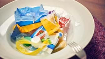Plate with plastic waste, bootle caps and a fork on a dining table