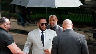 Musician R. Kelly, center, arrives at the Leighton Criminal Court building for an arraignment on new sex-related felonies Thursday, June 6, 2019, in Chicago. Thursday's hearing comes a week after prosecutors announced the new counts, including four of aggravated criminal sexual assault. (AP Photo/Amr Alfiky)