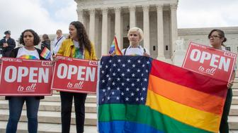 In this June 4, 2018 photo, American Civil Liberties Union activists demonstrate in front of the Supreme Court in Washington. The Supreme Court is ordering Washington courts to take a new look at the case of a florist who refused to provide services for the wedding of two men because of her religious objection to same-sex marriage.  The justices' order Monday means the court is passing for now on the chance to decide whether business owners can refuse on religious grounds to comply with anti-discrimination laws that protect LGBT people.   (AP Photo/J. Scott Applewhite)