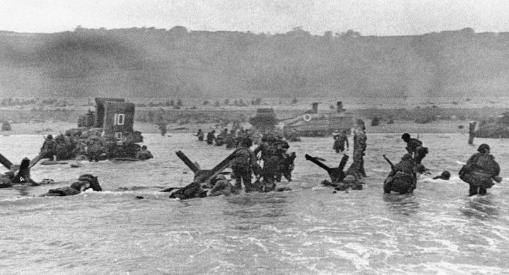 Some of the first assault troops to hit the Normandy, France beachhead on June 6, 1944 take cover behind enemy obstacles to f
