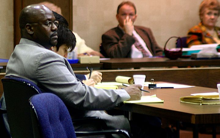 Curtis Flowers (left) listens to testimony in his third capital murder trial in Winona, Mississippi, onFeb. 6, 2004.