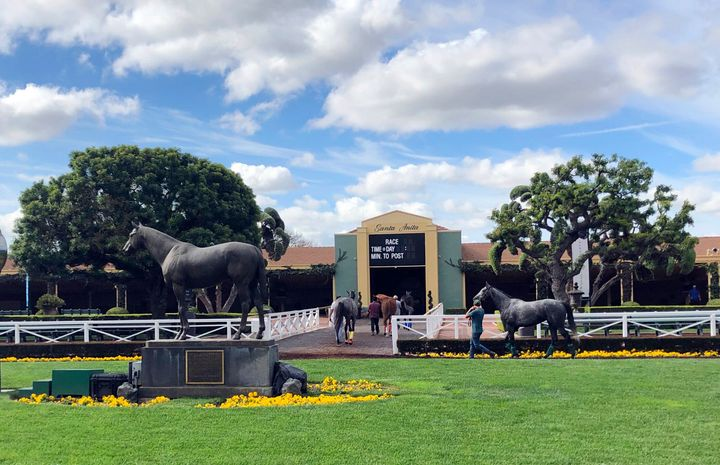 Horses are led to paddocks past the Seabiscuit statue during workouts at Santa Anita Park in Arcadia, California, on March 28