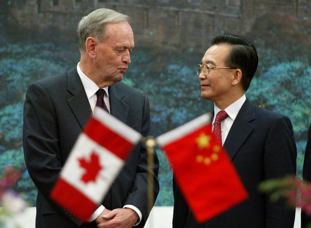Former prime minister Jean Chretien and then-Chinese Premier Wen Jiabao chat during a signing ceremony...