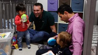 Elad Dvash-Banks, right, and his partner, Andrew, play with their twin sons, Ethan, left, and Aiden in their apartment Tuesday, Jan. 23, 2018, in Los Angeles. The toddler twins share almost everything: the same toys, the same nursery, the clothes and the same parents. Everything but a toothbrush and U.S. citizenship. Ethan became a plaintiff in a federal lawsuit against the U.S. State Department that seeks the same rights his brother has as a citizen. (AP Photo/Jae C. Hong)