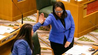 FILE - In this Jan. 9, 2017 file photo, Rep. Teresa Alonso Leon and Rep. Janelle Bynum, right, high-five after members of the House of Representatives are sworn into office at the Oregon State Capitol in Salem, Ore. Oregon is responding to a number of widely shared videos around the nation showing white people calling the police on African Americans going about everyday activities. The Senate voted 27-1 Monday, June 3, 2019, on a measure co-sponsored by Bynum, allowing victims of such 911 calls to take the caller to court for damages up to $250. (Molly J. Smith/Statesman-Journal via AP, File)