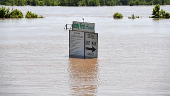 The Arkansas River floods along Adams Street Thursday, May 30, 2019, in Van Buren, Ark. (AP Photo/Michael Woods)