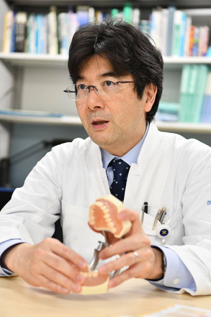 歯の模型を示しながら知覚過敏の原因について話す中川教授