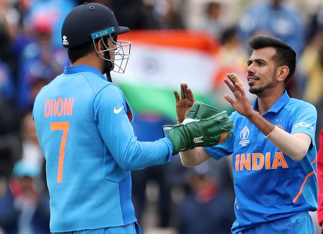 Yuzvendra Chahal, right, celebrates with teammate MS Dhoni the dismissal of South Africa's Andile Phehlukwayo...