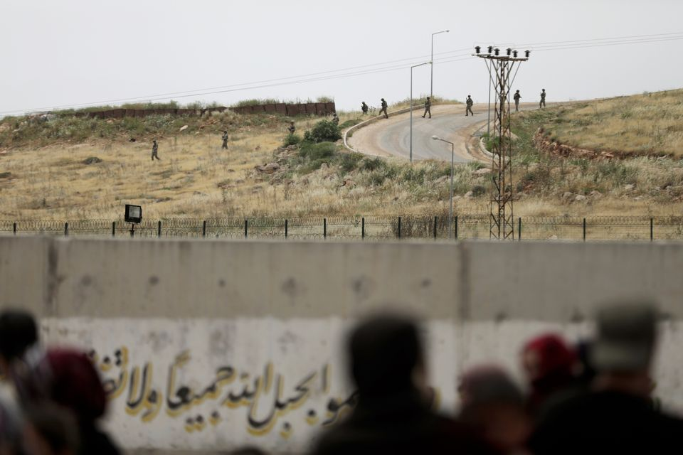 Turkish soldiers walk at the Atmeh crossing on the Syrian-Turkish border, as seen from the Syrian side,...