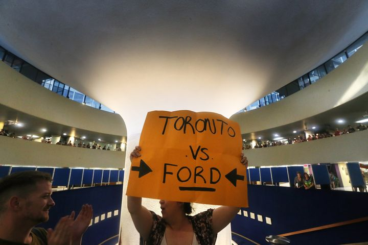 Protesters gather in Toronto city hall July 27, 2018 after an emergency motion pertaining to Premier Doug Ford's plan to cut the size of Toronto City Council down to 25 seats from the 47 seats.