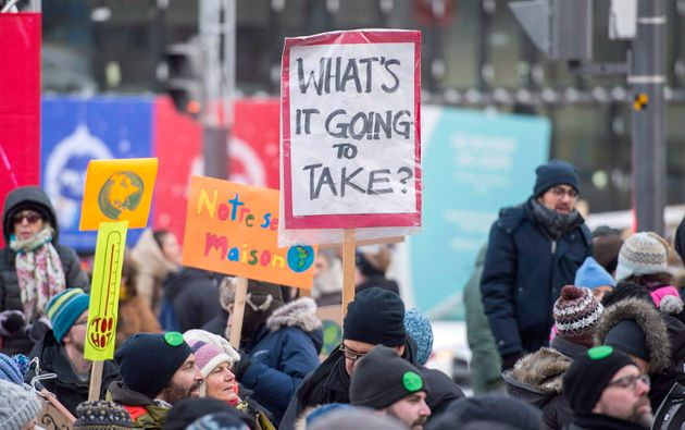 People hold up signs demanding action on climate change during a demonstration in Montreal on Dec. 8,
