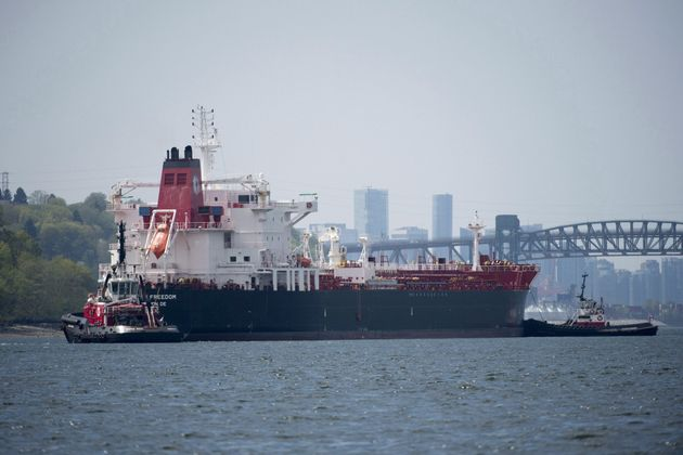 Tug boats prepare an oil tanker to go under the Second Narrows bridge after it left Kinder...