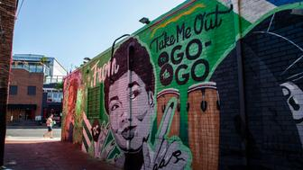 A mural decorates a building behind a Metro PCS store, Saturday, May 25, 2019 in the Shaw neighborhood of Washington. Go-go music, a distinctive Washington DC-specific offshoot of funk, has endured for decades through cultural shifts, fluctuations in popularity and law enforcement purges. Now go-go has taken on a new mantle: battle hymn for the fight against a gentrification wave that's reshaping the city.  (AP Photo/Alex Brandon)
