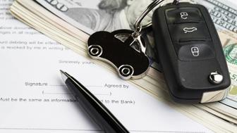 Buy or sell car, purchase or rent automobile service with key with car keychain on pile of US Dollar banknotes money on printed contract paper and pen to sign, finance installment or debt awareness.