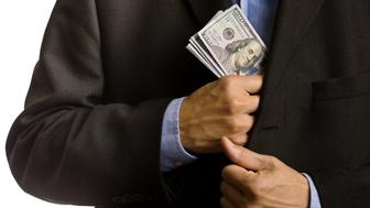 A businessman pocketing U.S. currency money, the dollar bills into his suit pocket. Concept photo of relationship between business and international trade. Photographed on white background in studio.