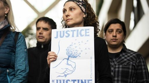 """A woman holds a sign that reads """"Justice for Justine."""""""