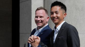Angus Leung Chun-kwong, a senior immigration officer, right, and Scott Adams, a same-sex couple who married in New Zealand pose for photographers outside the Court of Final Appeal in Hong Kong, Thursday, June 6, 2019. Hong Kong's Court of Final Appeal said Thursday the government cannot deny spousal employment benefits to same-sex couples, in a ruling hailed as a major step forward for same-sex equality in the semi-autonomous Chinese territory. (AP Photo/Kin Cheung)