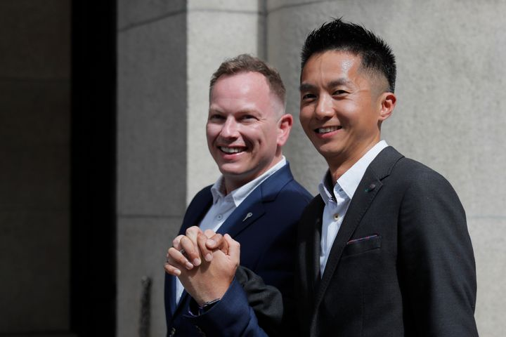 Angus Leung Chun-kwong, a senior immigration officer, right, and Scott Adams, a same-sex couple who married in New Zealand po