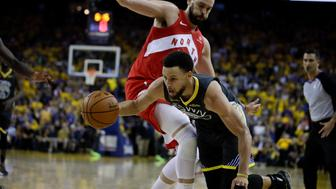 Golden State Warriors guard Stephen Curry, bottom, dribbles against Toronto Raptors center Marc Gasol during the second half of Game 4 of basketball's NBA Finals in Oakland, Calif., Friday, June 7, 2019. (AP Photo/Ben Margot)