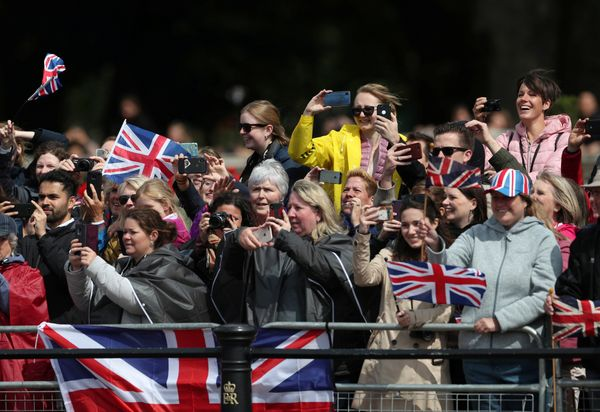 People on their cellphones as they watch the Trooping the Colour parade.