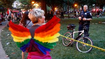 A police officer stands behind crime scene tape, Saturday, June 8, 2019, at Dupont Circle in Washington. Officials in Washington say several people were injured after a panic at the LGBTQ pride parade sent people running through the streets of the nation's capital. (AP Photo/Patrick Semansky)