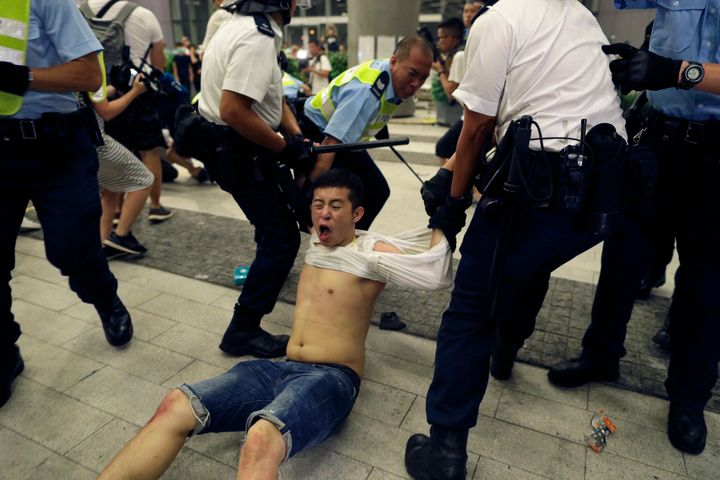 Hong Kong police officers drag away a protester during a rally against proposed amendments to the extradition law at the Legi