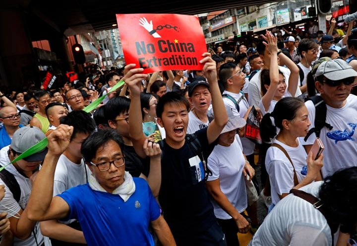 Protesters break through a police line as protesters march against the proposed amendments to an extradition law in Hong Kong