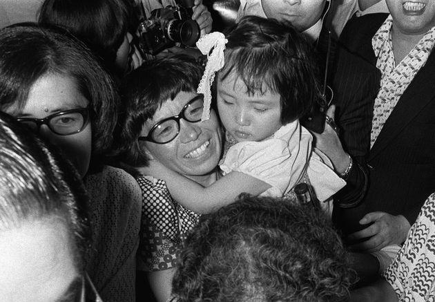 女性として世界で初めてエベレスト(チョモランマ)登頂に成功。帰国し、出迎えの娘・教子ちゃんを抱える田部井淳子さん(中央)(東京・羽田空港)1975年06月08日