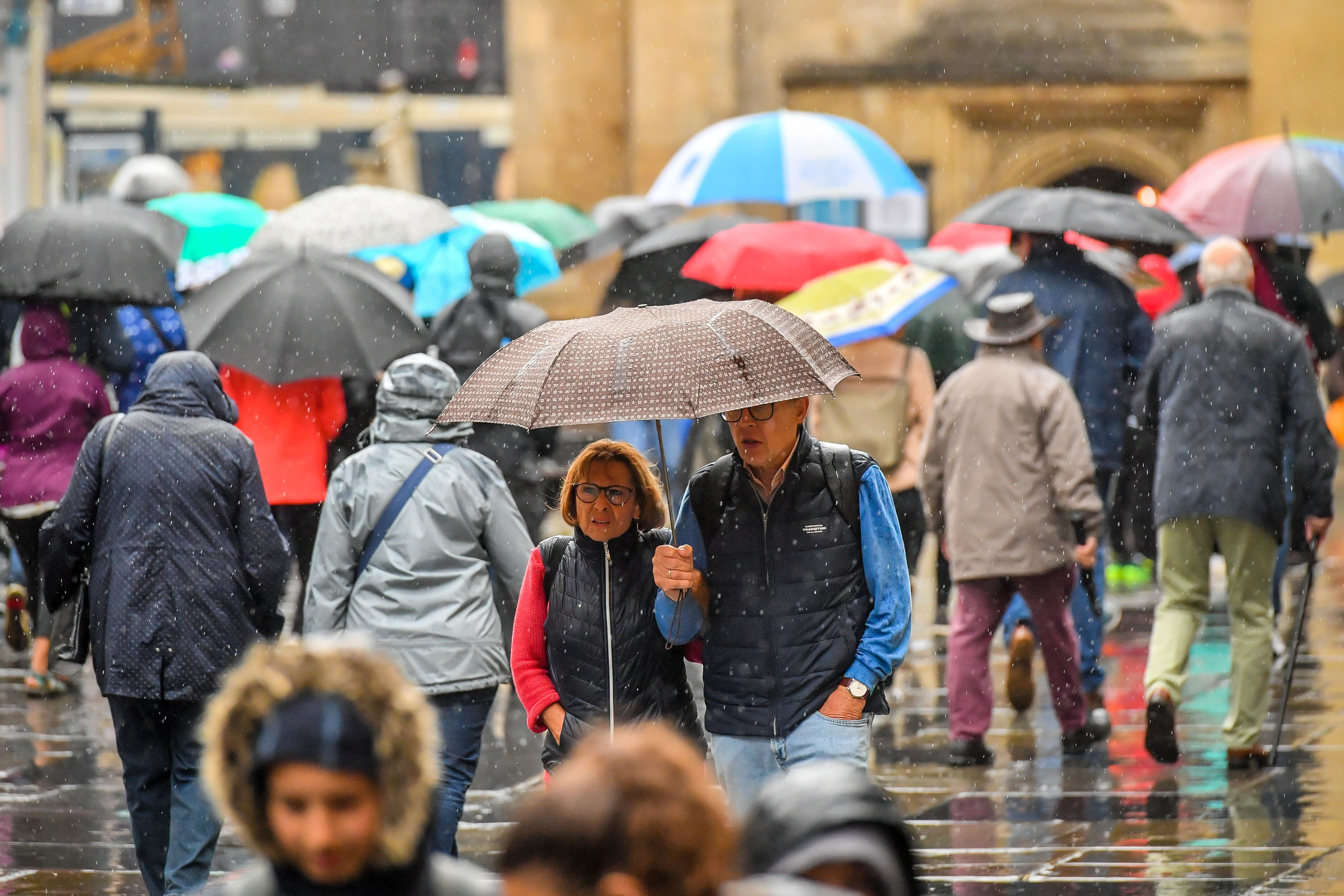 People use umbrellas as they cross Bath Abbey churchyard during a downpour in the centre of Bath (Picture: PA)