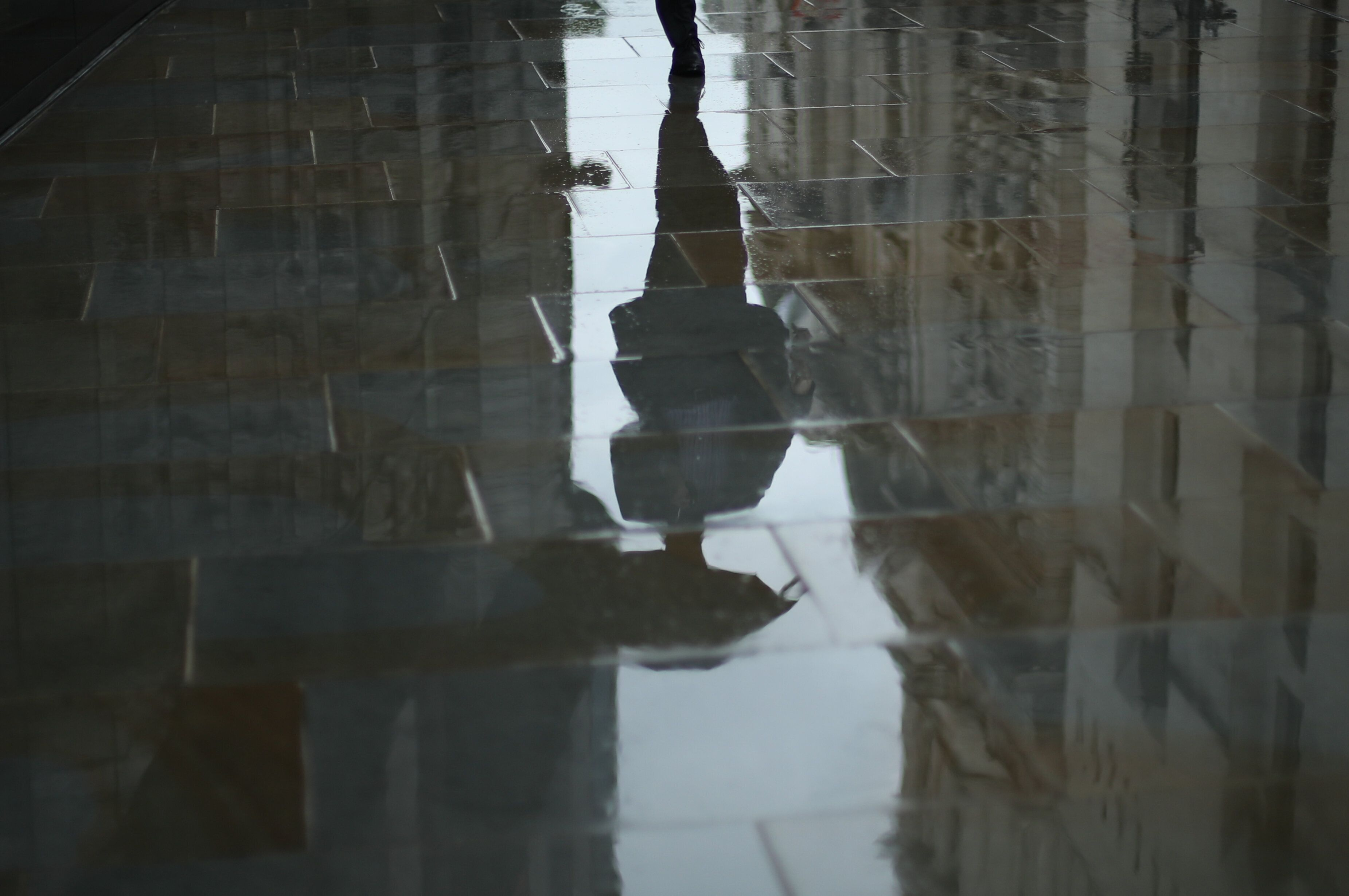 A man with an umbrella is reflected in the wet pavement outside the Old Bailey, London following a rain shower (Picture: PA)