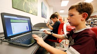 In this May 8, 2019, photo, third-grade student Miles Stidham uses an East Webster High School laptop to do homework in Maben, Miss. The Stidhams are unable to get internet at their home in the country, so they take advantage of the internet in the school's library. (AP Photo/Rogelio V. Solis)
