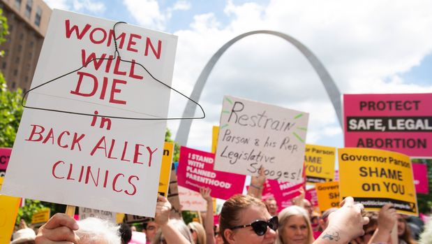 Protesters hold signs as they rally in support of Planned Parenthood and pro-choice and to protest a state decision that would effectively halt abortions by revoking the center's license to perform the procedure, near the Gateway Arch in St. Louis, Missouri, May 30, 2019. (Photo by SAUL LOEB / AFP)        (Photo credit should read SAUL LOEB/AFP/Getty Images)