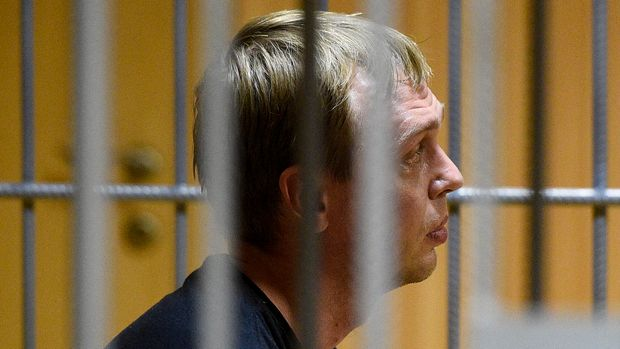 Ivan Golunov, a journalist who worked for the independent website Meduza, sits in a cage in a court room in Moscow, Russia, Saturday, June 8, 2019. A prominent Russian investigative reporter who was detained on drug-dealing charges has been released on house arrest in a case that has raised widespread alarm among journalists. (AP Photo/Dmitry Serebryakov)