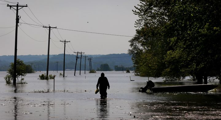 A resident wades through Mississippi River floodwater to his Winfield, Missouri, home on May 24.