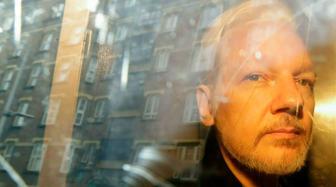 ARCHIVO - En esta imagen de archivo del miércoles 1 de mayo de 2019, edificios reflejados en la ventana mientras el fundador de WikiLeaks Julian Assange es trasladado desde el tribunal, donde compareció acusado de saltarse los términos de su fianza en Gran Bretaña hace siete años, en Londres. (AP Foto/Matt Dunham)