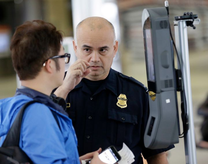 A U.S. Customs and Border Protection officer talks to a passenger at a face recognition kiosk at George Bush Intercontin