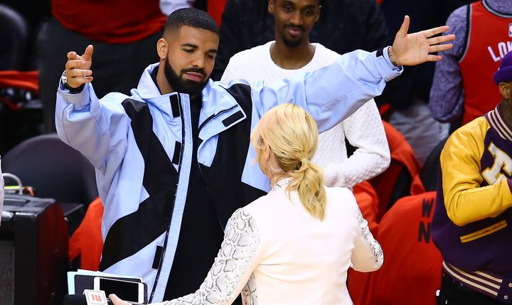 "Drake greets TV personality Doris Burke before Game Five of the NBA playoffs. This was taken mere minutes before his emotional singalong to ""O Canada."""
