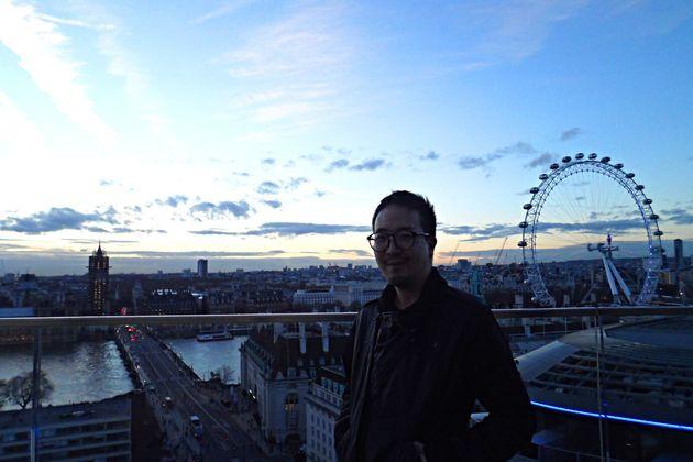 귀국 직전, 친구의 기숙사 건물에서 웅장한 런던의 경치를 등지고 서있는 제