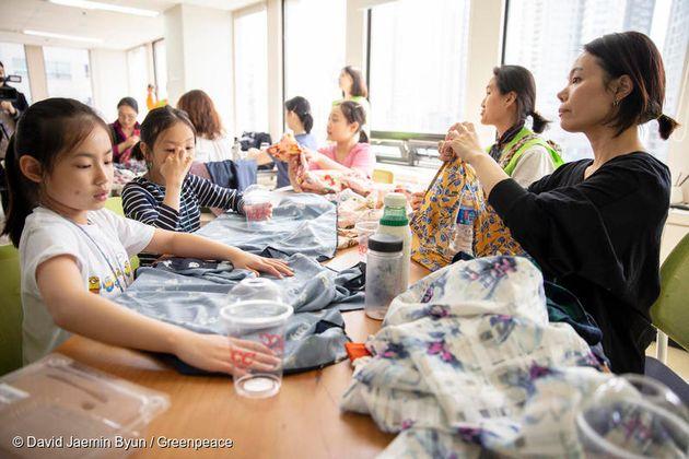 선물 포장 연습을 위해 집에서 가져온 재료로 연습하는 가족 참가자들