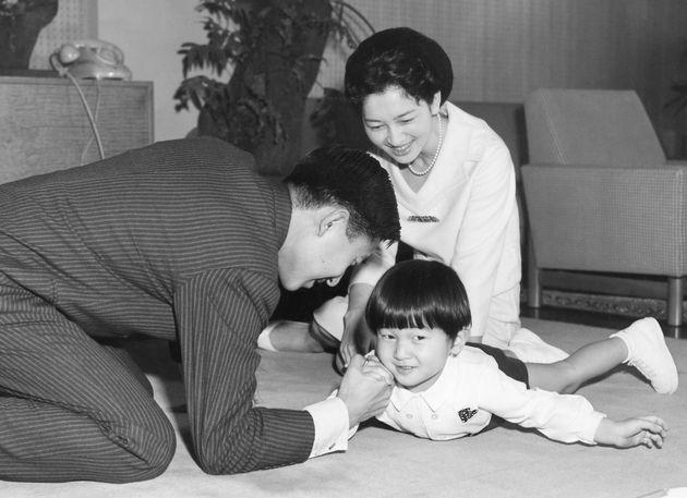 天皇陛下(当時)と腕相撲をされる浩宮さまと見守られる美智子さま=1964年2月、東京都港区の東宮御所
