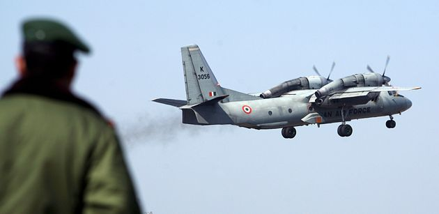 A soldier stands guard as an Indian Air Force AN-32 transport aircraft takes off from the technical airport...