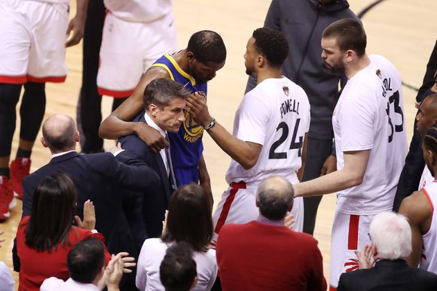 Kevin Durant of the Golden State Warriors is assisted off the court after sustaining an injury in the...