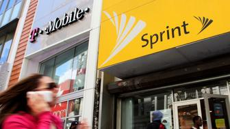 FILE - In this April 27, 2010 file photo, a woman using a cell phone walks past T-Mobile and Sprint stores in New York. Published reports say a group of state attorneys general are planning a lawsuit to block a $26.5 billion merger of wireless carriers T-Mobile and Sprint. It's an unusual step ahead of a decision by federal antitrust authorities. (AP Photo/Mark Lennihan, File)